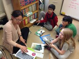 Image of teacher working with three children on a computer