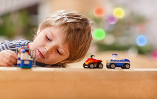 Little boy playing with car toys